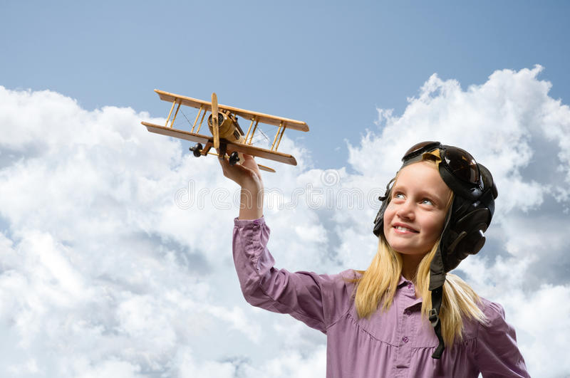 Girl in helmet pilot playing with a toy airplane. Girl in helmet pilot playing with a toy wooden airplane in the clouds, dreaming of becoming a pilot stock image