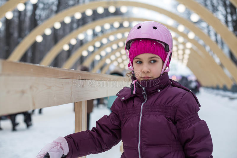 The girl in helmet skates in the park. The girl in pink helmet skates in the park stock image