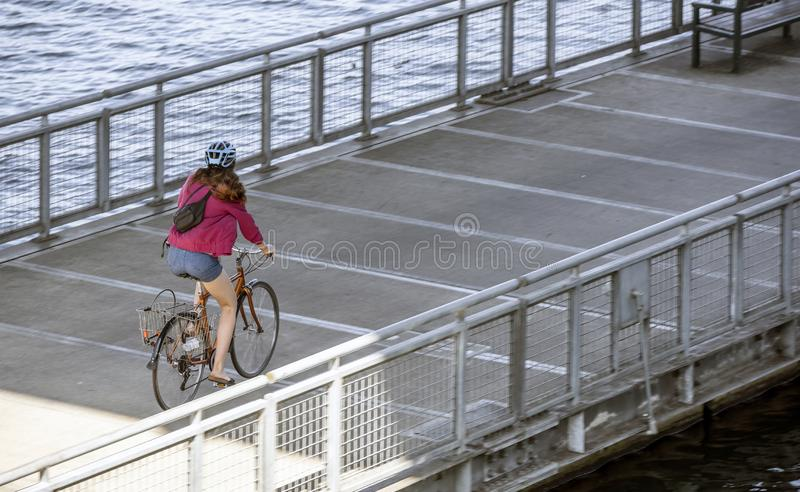 Girl in a helmet takes a bike ride on a floating dock on the river royalty free stock photo