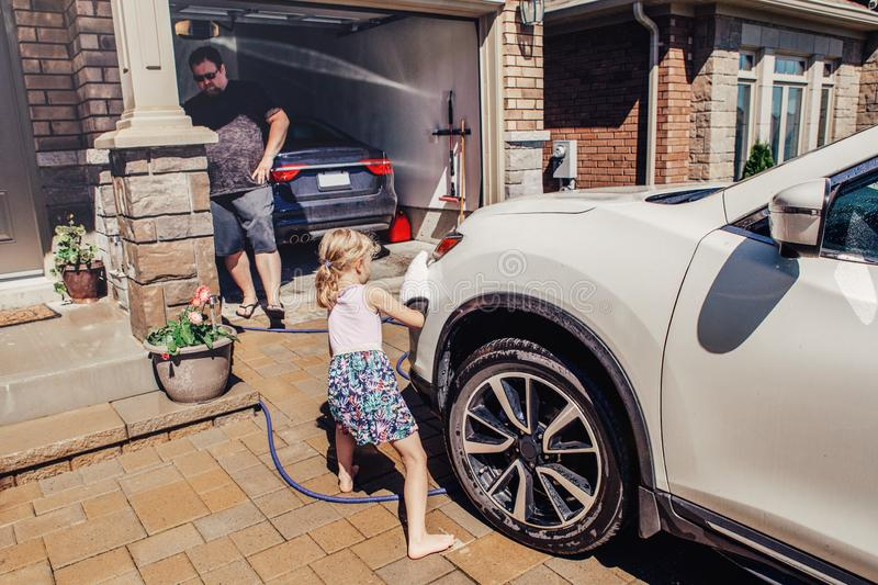 Girl helping father wash car on driveway in front house on summer day. Cute preschool little Caucasian girl helping father wash car on driveway in front house on royalty free stock images