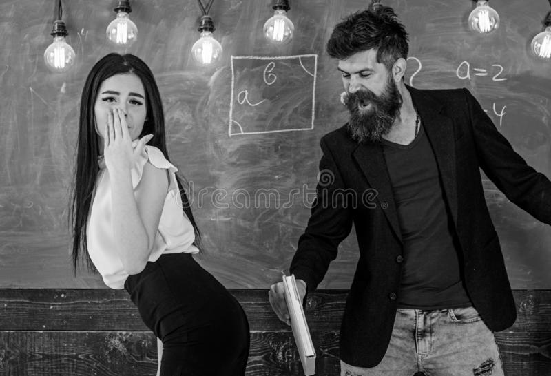 Girl on helpless face punished by teacher. Schoolmaster punishes student with slapping on her buttocks with book royalty free stock photos