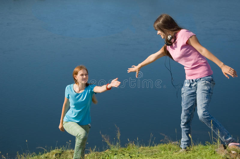 A girl helps her friend up. The hill stock photo