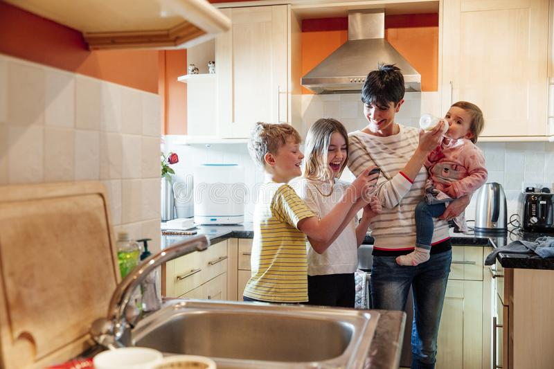 Multitasking Mum with her Children at home royalty free stock photos