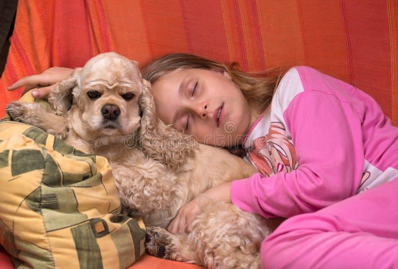 Girl and her dog sleeping together stock photography