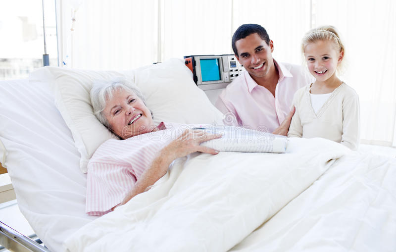 A girl with her father visiting her grandmother. Smiling little girl with her father visiting her grandmother at the hospital stock photography