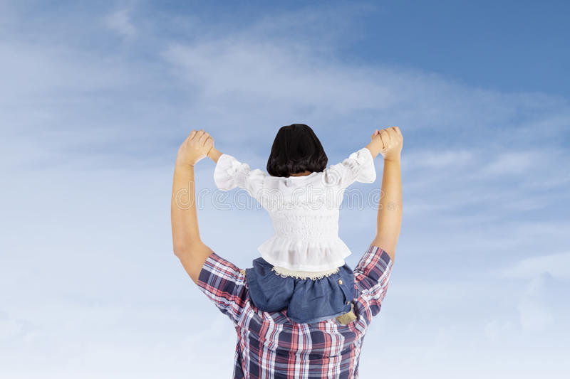 Girl on her fathers back. Girl is being carried by her father at the back under blue sky