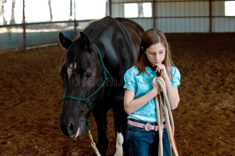 A girl and her horse. A young girl and her Quarter Horse pause during a Parelli instruction session. The girl holds a carrot stick with a sassy string royalty free stock images