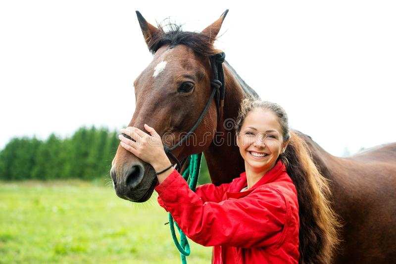 Girl with her horse. Beautiful smiling girl with her brown horse outdoors stock images