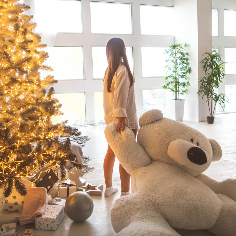 Girl in her house on Christmas with a big bear and a beautiful d stock photo