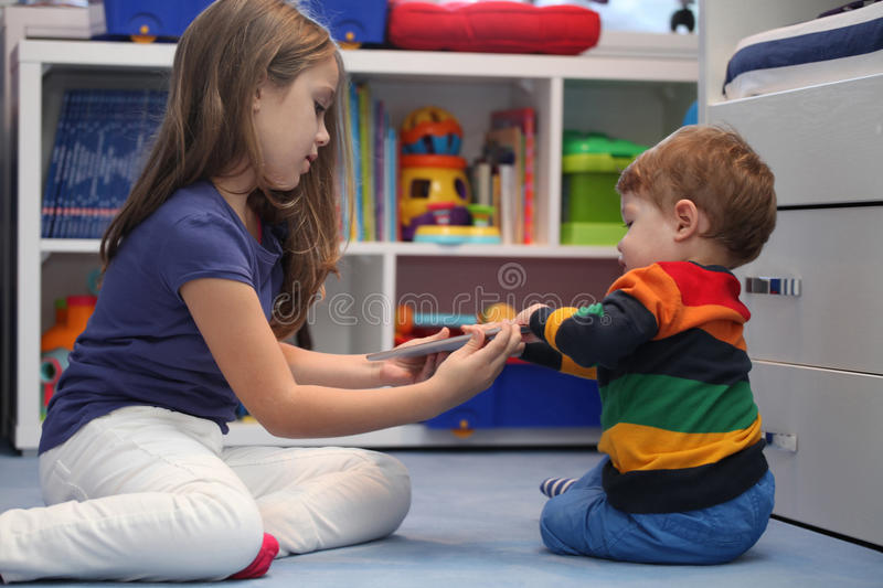 Girl and her little brother arguing with a digital tablet comput. Er royalty free stock image