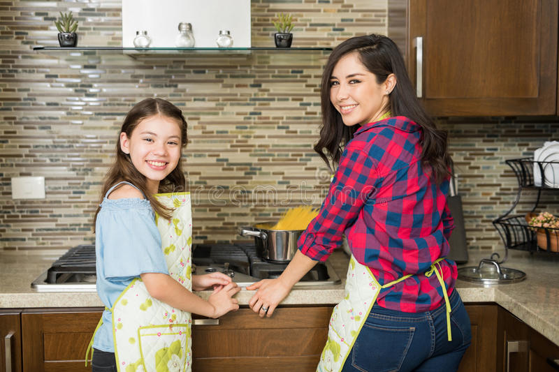 Girl and her mom cooking dinner at home stock image