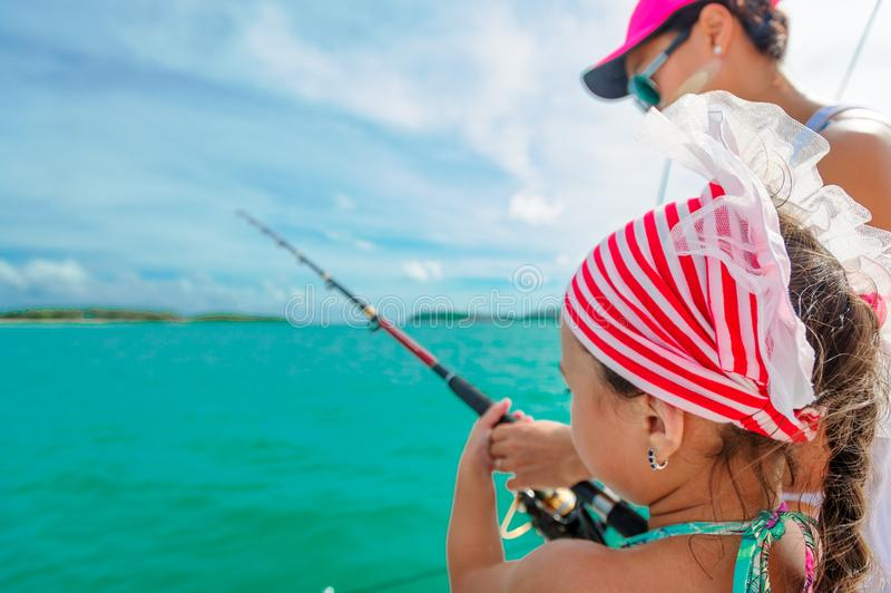 A girl and her mom fishing on a boat. Colorful tropical pattern. Around royalty free stock photo