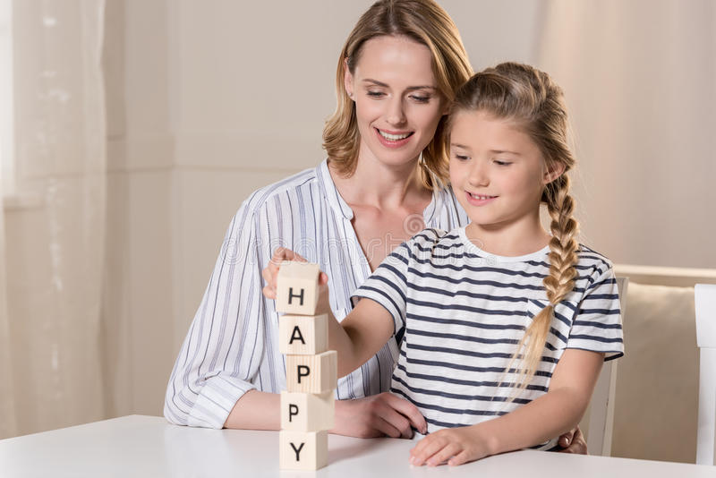 Girl and her mother composing word Happy using wooden cubes. Young girl and her mother composing word Happy using wooden cubes royalty free stock images