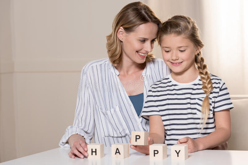 Girl and her mother composing word Happy using wooden cubes. Young girl and her mother composing word Happy using wooden cubes stock photos