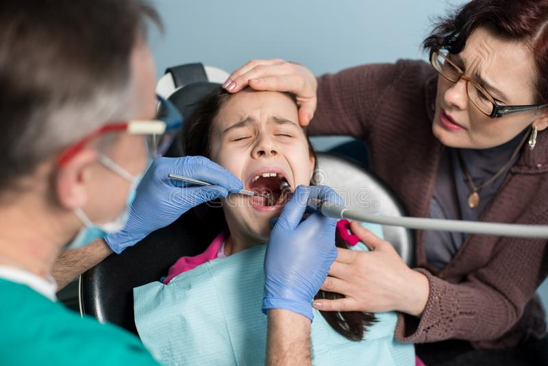 Girl with her mother on the first dental visit. Senior male dentist drilling patient teeth at the dental office. Dentistry, medicine, stomatology and health stock photo