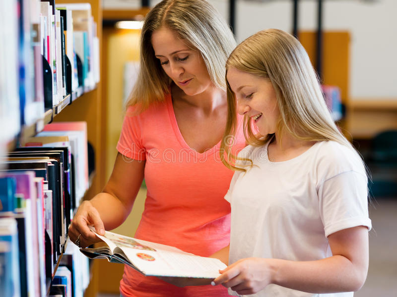 Girl and her mother in library royalty free stock photo