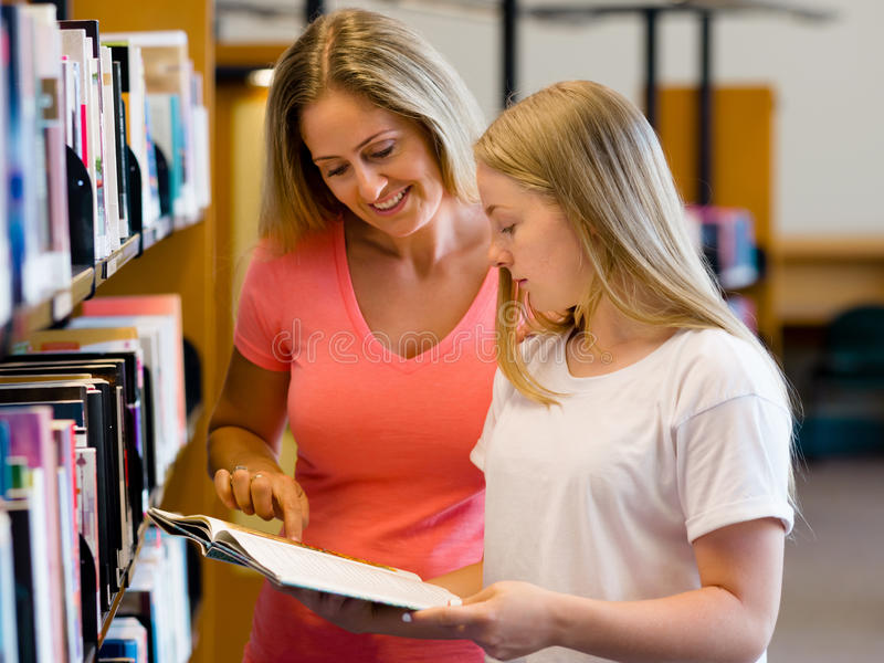 Girl and her mother in library royalty free stock image