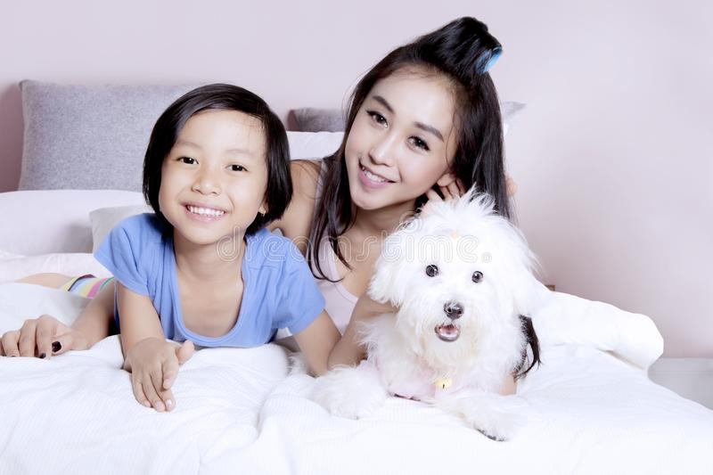 Girl with her mother and Maltese dog stock photo