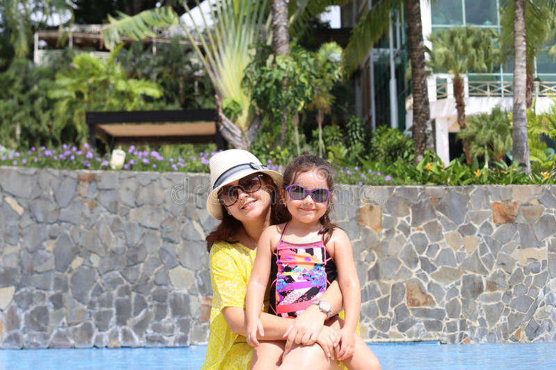 Girl with her mother outside swimming pool enjoying the summerwith their sunglasses royalty free stock images
