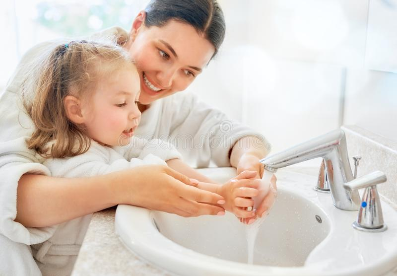 Girl and her mother are washing hands royalty free stock image