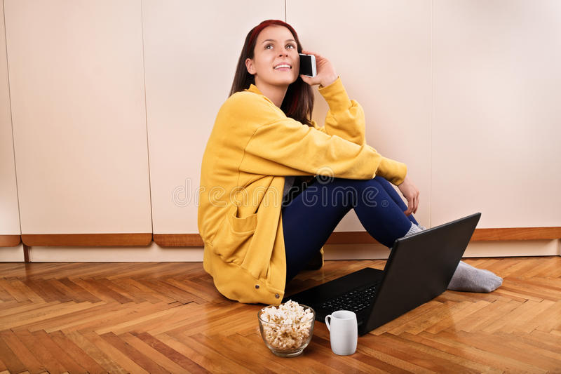 Girl in her room talking on the phone. Girl talk. Young girl in front of her laptop eating popcorn and talking on the phone stock image