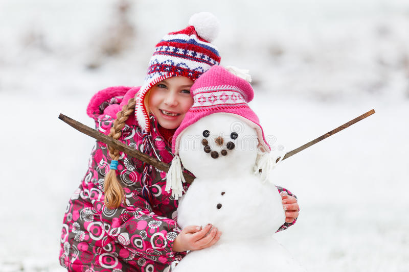 Girl with her snowman winter fun royalty free stock photo