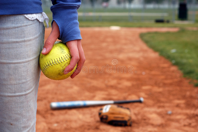 A Girl and Her Softball, Glove. A girl holds a softball on the infield diamond royalty free stock image