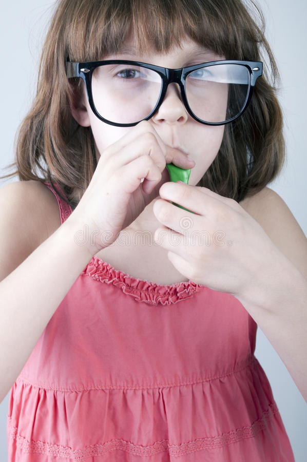 Girl with herd sunglasses blowing a balloon royalty free stock photography