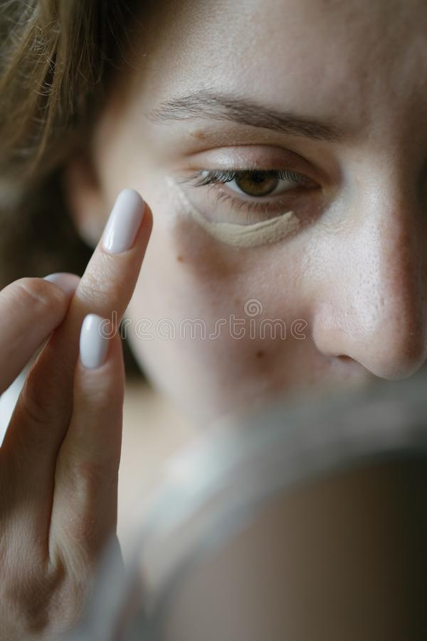 The girl hides bruises under her eyes with makeup. A woman`s face is a close-up stock photo