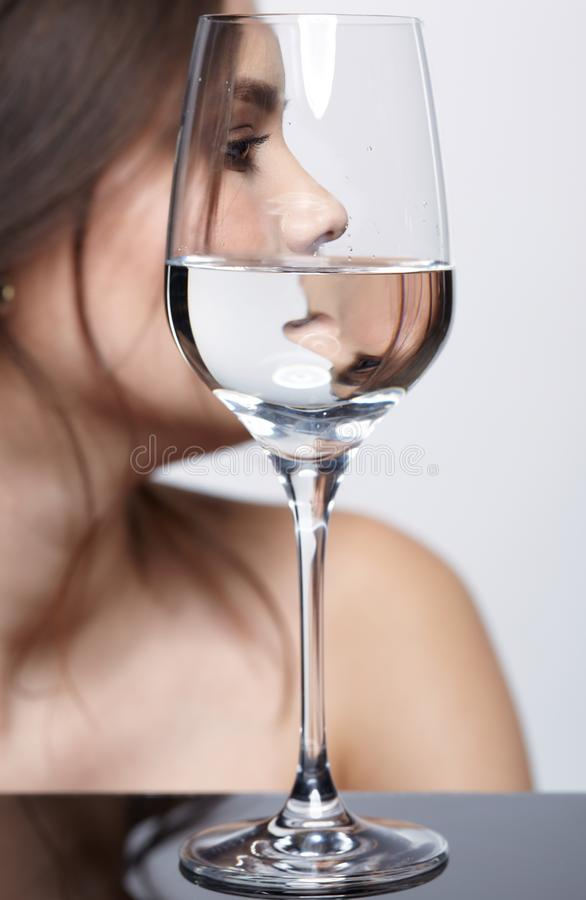 Girl hides her face behind a glass glass of water. Beauty portrait of young woman on gray background royalty free stock photo