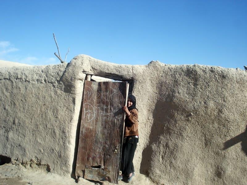Girl hiding behind a door in Afghanistan stock image