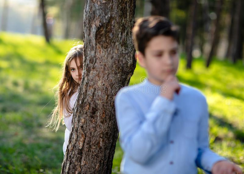 Boy and girl playing hide and seek in the park. Girl watching on boyfriend. stock images