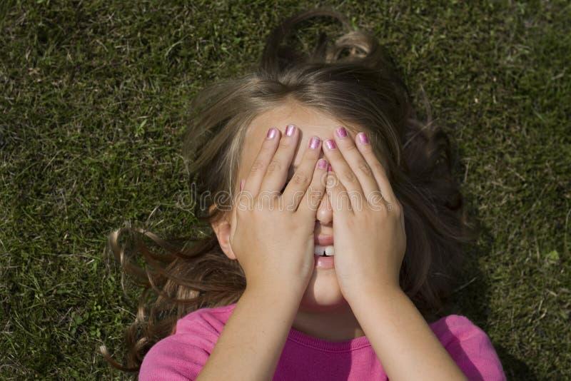 Girl hiding face stock photography