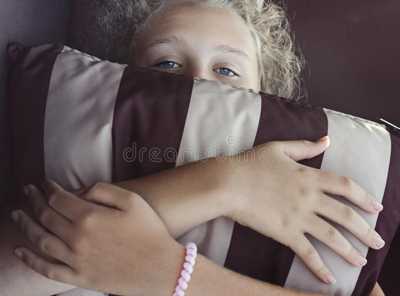 Girl is hiding her face by striped pillow royalty free stock photos