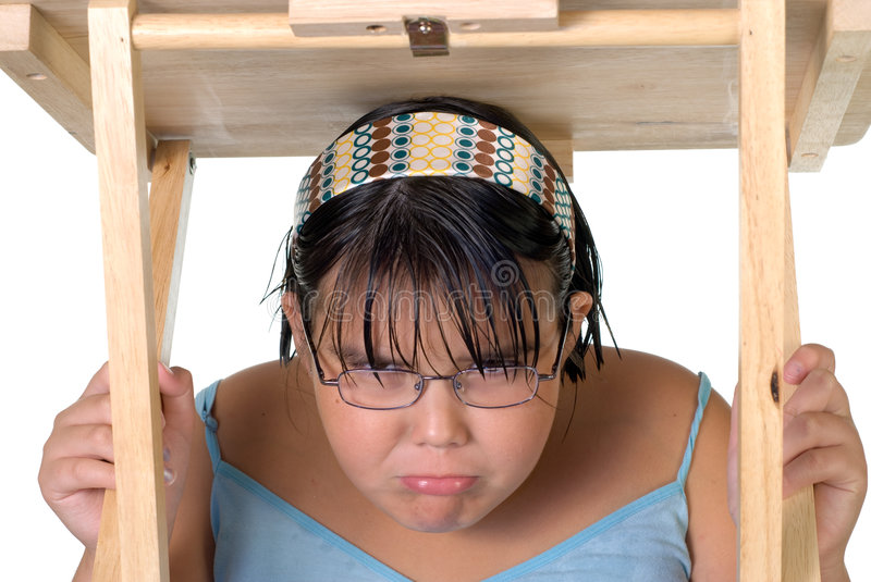 Girl Hiding Under Table. A young caucasian girl hiding under a table, isolated against a white background royalty free stock image
