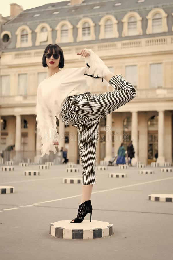 Girl in high heel shoes, fashionable clothes in paris, france. Woman stretch leg on square. Fashion, beauty, style, lifestyle. Yoga, pilates, fitness sport royalty free stock photo