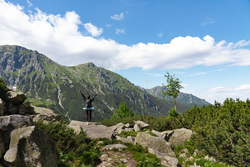 Girl hiker with backpack standing near the top of the mountains with raised hands, active life concept royalty free stock photos