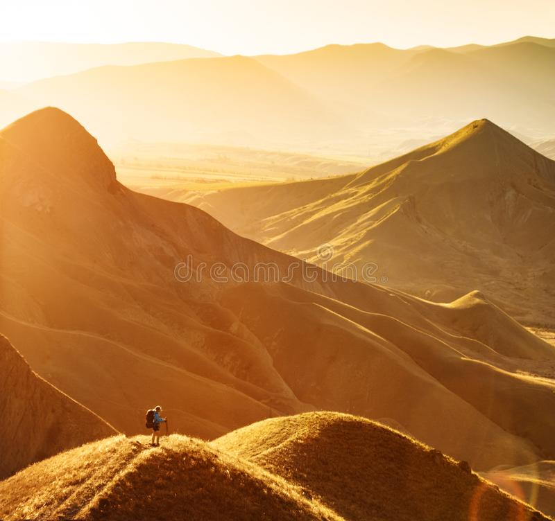 Girl hiker contemplate the mountain valley. Girl hiker with backpack and trekking sticks standing on a hill and contemplate the mountain valley. Travel and stock photography
