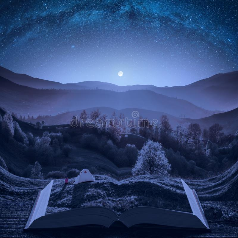 Girl hiker near the camping tent under the night starry sky. In a mountain valley on the pages of an open magical book. Majestic landscape. Nature and education stock photo