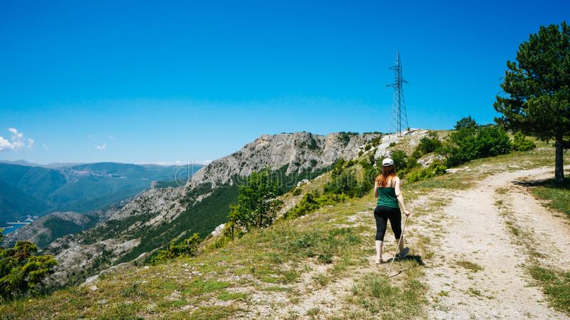 Girl hiker walking along a pathway with her backpack. Sport caucasian woman jogging in summer with hat and wood stick. Red head royalty free stock photography