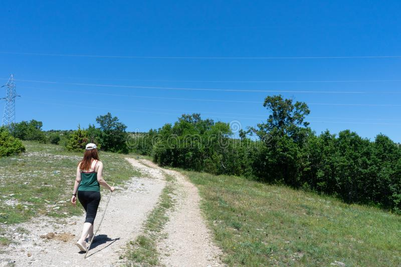 Girl hiker walking along a pathway with her backpack. Sport caucasian woman jogging in summer with hat and wood stick. Red head royalty free stock photo