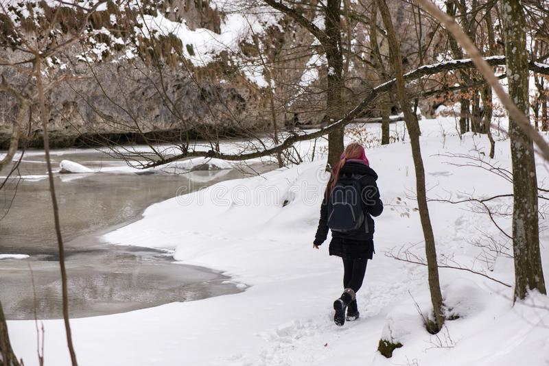 Girl hiking in cold, white winter. royalty free stock image