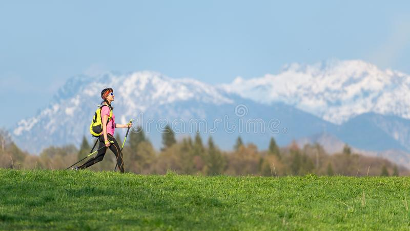 Girl hiking in the mountains with spring contrasts of green meadows and snow on the mountains stock images