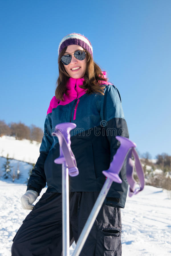 Girl with hiking sticks on the snowy mountain. Girl with hiking sticks on the snow covered mountain royalty free stock image