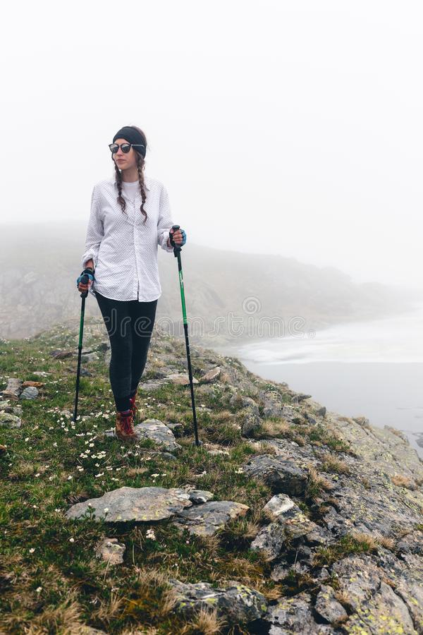 Girl hipster travels rocky mountains. royalty free stock photography