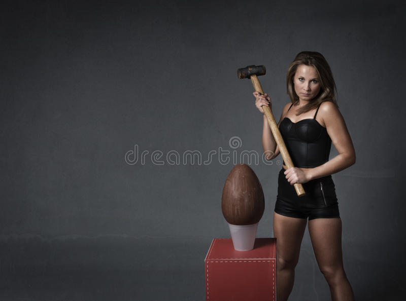 Girl hit easter egg. Girl in dark background ready for easter holiday stock photos
