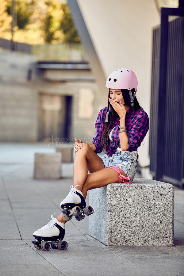 Girl hit a leg while roller skating in urban skate park royalty free stock photography