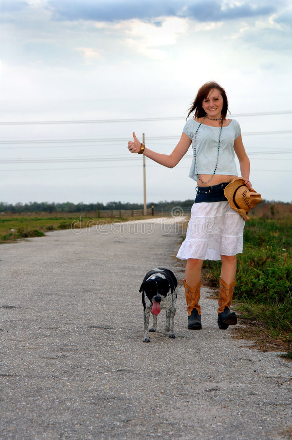 Girl hitchhiking with her dog. A young woman in cowboy boots with her dog hitchhiking alone on a country road royalty free stock photos
