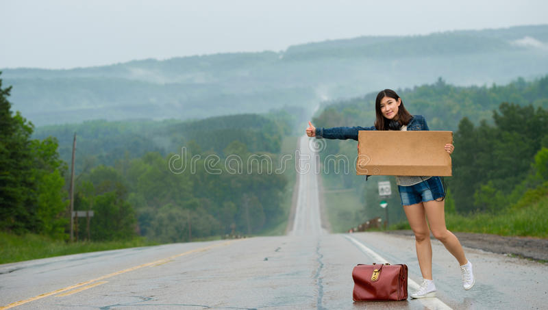 Girl hitchhiking holds up a sign stock photo