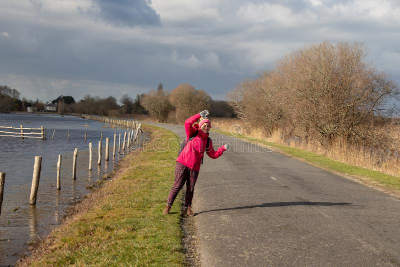 Girl hitchhiking on a rural road wearing a pink c. Young backpacker hitchhiking on a rural road wearing a pink coat stock photo